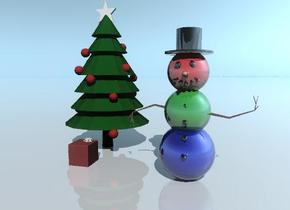 The head of the shiny snowman is red. the midbod of the snowman is green. the bottom of the snowman is blue. The ground is shiny.  The christmas tree is behind the snowman. it is to the left of the snowman. The gift is in front of the tree. the ribbon of the gift is pink.