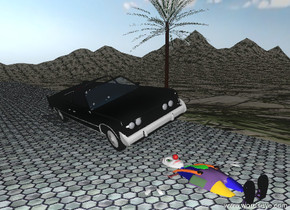 The leaning  car is on the wide tile driveway.  the driveway is 200 feet long. The driveway is on the tall mountain range. the mountain range has a grass texture.  It is partly cloudy.  The tiny palm tree is to the right of the car.  The face-up clown is in the driveway.  The clown is in front of the car.