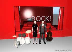 "There is a drum. There is a 4 foot tall man 2 feet in front of the stage. The small drum is to the left of the 4 foot tall woman. There is a guitar on the stage. There is the 4 foot tall woman next to the man. There is a ""ROCK!"" on top of the stage. The small vp12529 is to the right of the man. The stage is red."