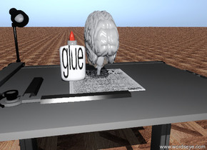"the thin brain is on the paper. the glue is next to the brain. the paper is on the table. the ground is parquet. the small ""glue"" texture is on the glue."