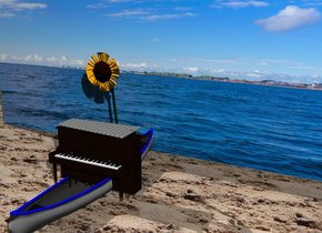 the [sky] wall. the canoe is in front of the wall. the ground is sand.the small piano is in the canoe. The xylophone is on the piano. The sunflower is in back of the piano.