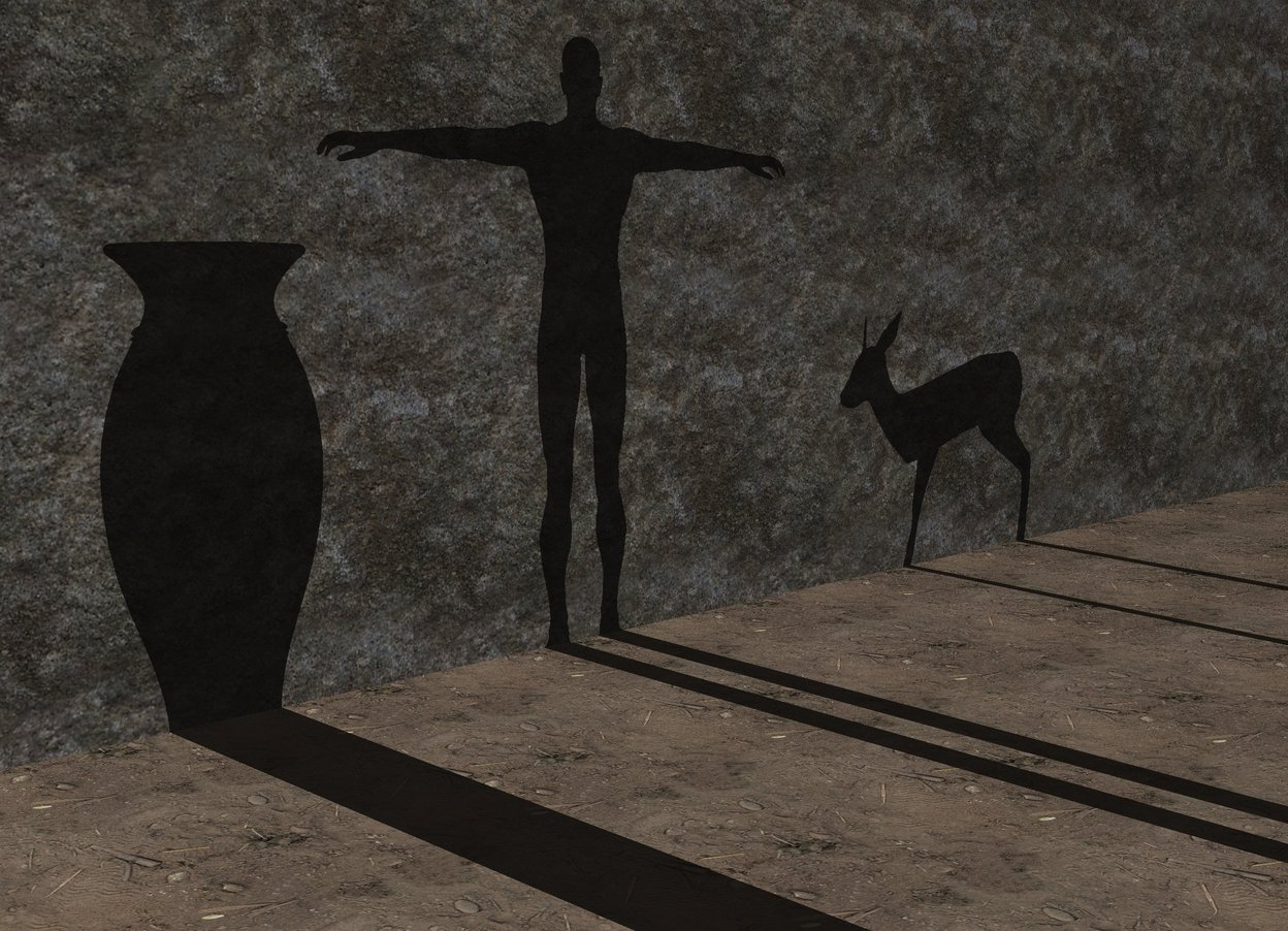 Input text: the man is in front of the huge wall. he is 20 feet away from the wall. he is facing the wall. the wall has a rock texture. the ground is dirt.  the white illuminator is 120 feet in front of the wall. the camera light is black.  the big vase is 20 feet in front of the wall. it is next to the man. the deer is 20 feet in front of the wall. it is facing left. it is 1 feet to the right of the man.