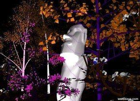 There are 12 trees on grass on a dark green ground. There are 12  flowers 3 feet in front of the trees. There are 12 shrubs behind the trees. It is night. There is a large stone idol behind the flowers. A huge white light is in front of the idol.
