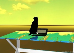 The dog faces backwards.  There is a computer behind the dog.  The computer is large. The dog is small.  The computer is on top of a desk. The dog is above the desk. The desk is a map. The ground is black and white. It is noon. The sun is yellow.