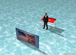 A teacher is in front of a red table. Books are on the table. Sky is dark. Ground is water. Big American flag is 10 feet in front of the teacher.