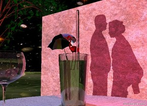 there is a glass on a white fabric table. a very tiny bright red flamingo is 2 inches in the glass. a clear cylinder is to the right of the flamingo. it is 8 inches tall and .4 inches wide. a very tiny [party] umbrella is -1.5 inches to the left of the flamingo. it is -1.5 inch above the glass. it is leaning to the right. the stone wall is 7 feet behind the table. it is 20 feet wide. a tiny red light is 2 inches to the right of the flamingo.   the man is in front of and 2.5 feet to the left of the table. he is 2.6 feet tall. he is facing right. the white light is 4 feet in front of the man. the woman is -2 inches to the right of the man. she is facing the man. she is 2.4 feet tall. the wine glass is 3 inches in front of and to the left of the glass.  the camera light is black. the mauve light is 2 feet above the wine glass. the [sky] texture is on the sky. the texture is 1000 feet tall.  the ground is shiny grass.  a small tree is -2 feet to the left of the wall.