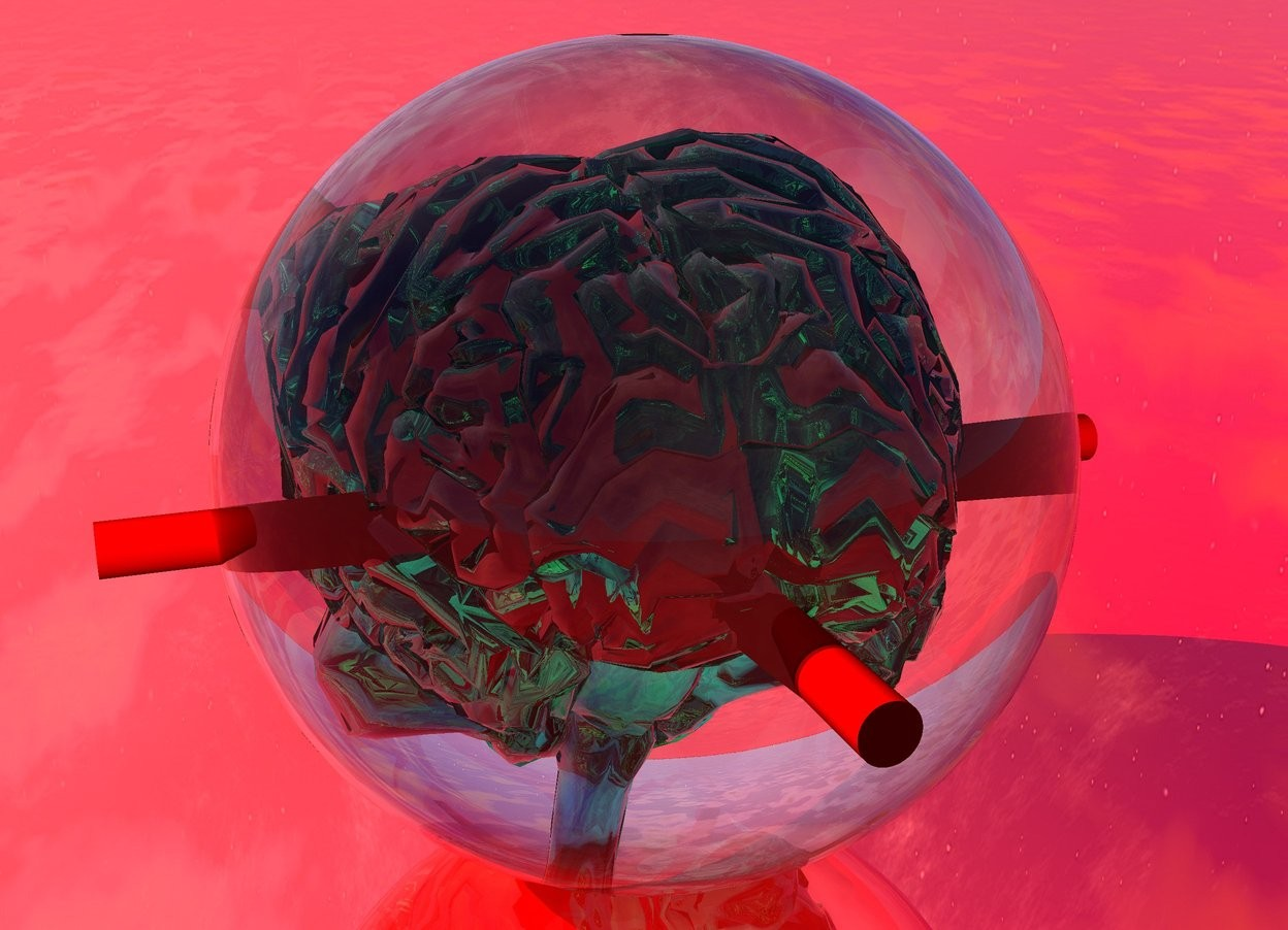 Input text: there is a clear 2 feet tall sphere. a 1.2 feet tall clear spring green brain is 1.7 feet in it. the ground is shiny red. a 1st tiny red 2.5 feet long cylinder is 8 inches in the brain. it faces up. a 2nd tiny red 2.5 feet long cylinder is 1 inches in the 1st red cylinder. it faces up. it faces east.