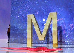 """the gold """"M"""" is a couple of feet in front of the shiny [electric] wall. the wall is 4 feet high and 6 feet wide. the ground is shiny. It is cloudy. the tiny man is to the left of the wall.  the small red shiny snake is a foot in front of the """"M"""". it is facing right."""