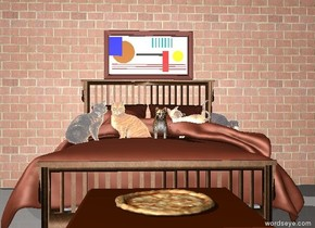 There is a bed on the ground. There are 5 small cats on top of the bed. There is a long tall brick wall behind the bed. There is a painting on the wall above the bed. There is a table in front of the bed. There is a pizza on the table.