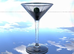 the dark green olive is -1.5 inches above the top of the martini glass. the ground is silver.