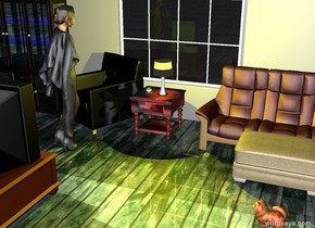 The cup is on the table to the left of the lamp. The table is to the right of the chair. The lamp is on the table. The huge wall is behind the chair. The coffee table is facing the chair. The coffee table is 4 feet in front of the chair. The yellow light is in the lamp. The ground is wood. The huge wall is grey. The cabinet is to the left of the chair. The ottoman is in front of the couch. The television is on the coffee table.The couch is 3 feet to the right of the chair. The window is 1.5 feet behind the lamp.  The sky is light blue. The woman is in front of the chair. The woman is facing the cup. The dog is 2 feet in front of the ottoman. The dog is facing the woman.