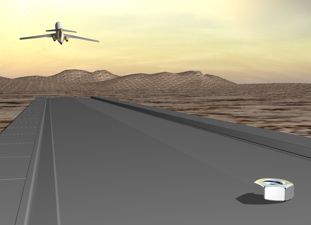 Input text: a very tiny plane above a very long narrow grey street. the plane is 7 feet above the street. the plane is leaning to the back. a huge silver hex nut is on the street. the hex nut is 60 feet behind the plane. the ground is sand.