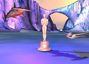 the oscar trophy.  the tiny shark is left of the oscar. it is facing southeast. it is 10 inches above the ground.   the tiny ray is right of the oscar. it is 4 inches above the ground. it is facing southwest.  an blue light is above the oscar. a red light is 3 inches in front of the oscar.