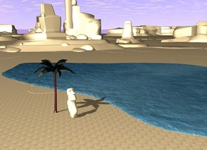 the ground is sand. there is water on the ground. there is a  small palm tree near the water. there is a statue in front of the plant.