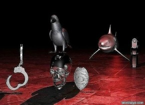 The parrot is on a silver skull. A red light is above the parrot. The ground is rocky. A shark is 5 feet behind the skull. Handcuffs is three inches to the left and two inches in front of the skull. A large gun is 1 inch in front and 1/2 an inch to the right of the shark. A badge is 1 inch to the right of the skull. It is night. There is a red light behind the shark.