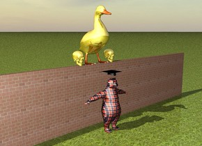 It is afternoon and the ground is grass. A plaid bear is a couple of feet in front of a brick wall. The wall is 50 feet long and 9 feet high. There is a large black graduation cap on the bear. A giant gold duck is on the wall. A big gold skull is on the left of the duck. A big gold skull is on the right of the duck.
