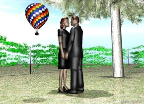 Woman is on the ground. The ground is grass. The grass is green. There is a light two feet above the woman. The woman is facing a man. The man is facing the woman. It is noon. There is a tree. The tree is to the right of the woman. The man is in front of the woman. There is a hot air balloon. The hot air balloon is 2 feet tall. The hot air balloon is 2 feet to the left of the woman. The hot air balloon is 4 feet above the ground. There is a hedge.The hedge is 50 feet long. The hedge is behind the tree. The hedge is 7 feet tall. There is a hedge. The hedge is to the right of the tree. The hedge is 50 feet long. The hedge is 7 feet tall. The hedge is facing the tree.