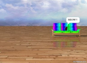 The cat is on a couch. The couch is Rainbow. There is a wood ground.