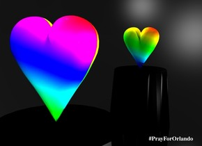 A [rainbow] heart is on a black table. the Sky is black.ground is silver. There is a large light on the heart. There is a large rainbow light facing the table. there is an enormous mirror 2 feet behind the table. the mirror is 30 centimeters in the ground.