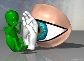 giant eyeball faces towards the green baby. Hand is facing toward the baby