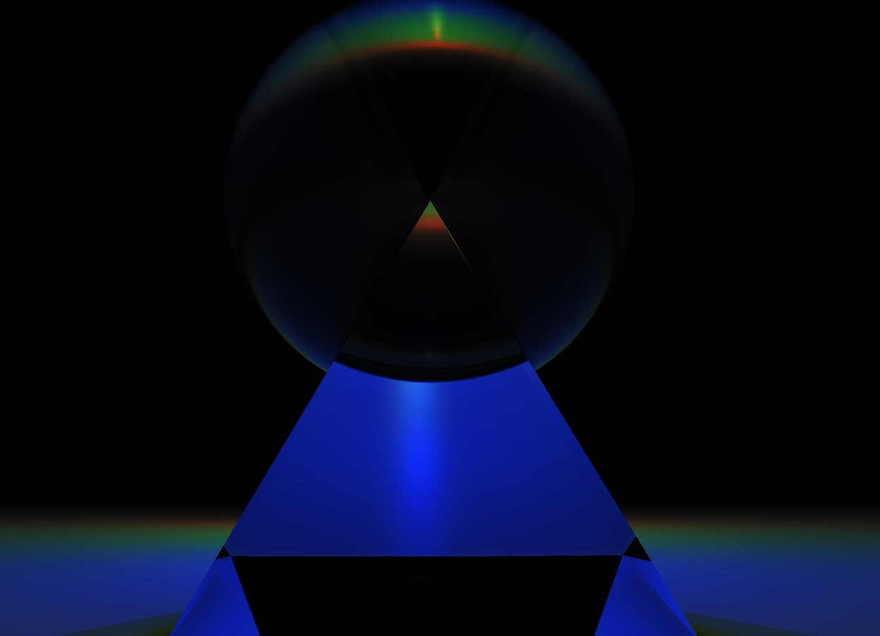 Input text: a clear sphere in a clear pyramid.  a couple red lights.  a few blue lights.  several green lights.  it is night.