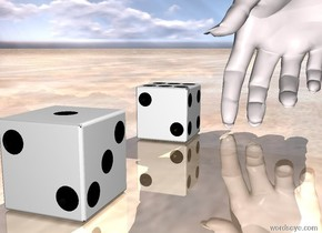 a first die.a second die is 3 inches left of the first die.the second die is upside down.the first die is facing north.a hand is behind the second die.the hand is pale pink.the ground is shiny wood.the hand is left of the second die.the first die is facing southwest.