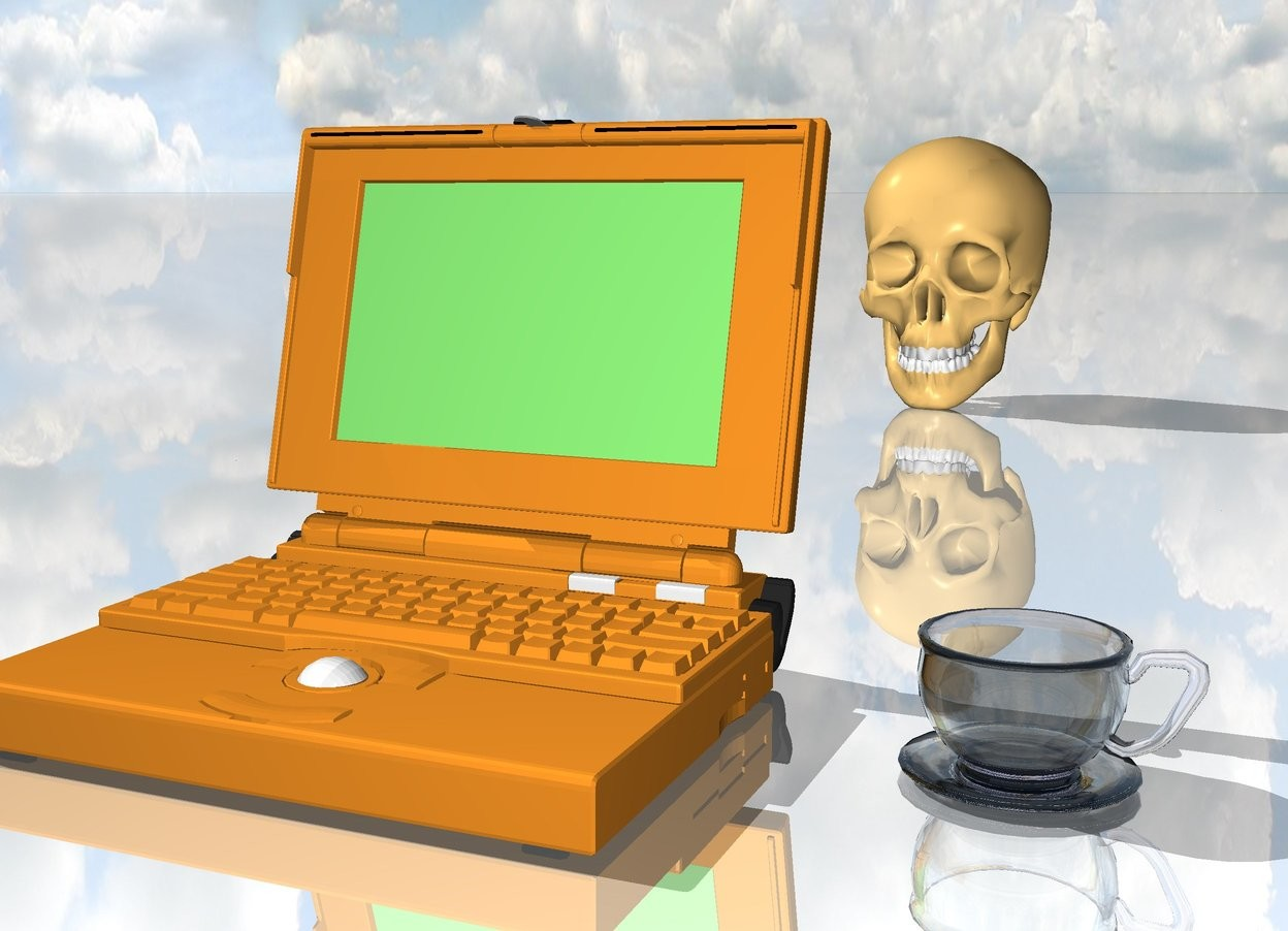 Input text:   laptop is on the shiny ground 3 inches away from the clear cup.  the skull is 3 feet behind the laptop.