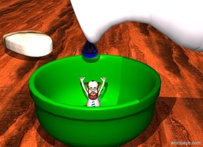 a green bowl.a 2 inch tall man is -0.2 feet above the bowl.a small white jug is -5.1 inches right of the bowl.the jug is leaning 110 degrees to the east.the jug is 2.3 inches above the ground.a large clear blue drop is 0.9 inches above the man.the ground is wood.the camera light is lilac.a soap is 6 inches behind the bowl.the soap is facing southwest.the soap is left of the bowl.the soap is rock.it is noon.a white light is in front of the man.