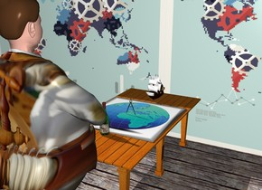 a table.a [map] picture is on the table.the picture is face up.a shiny black compass is above the picture.a 12 inch tall galleon is behind the picture.a man is in front of the table.the man is facing the table.a flat wall is behind the table.the wall is [chart].the man's dress suit is [ancient].a bottle is in front of the picture.the bottle's label is fruit.the ground is wood.