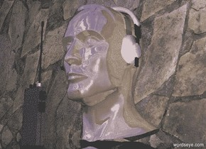 a shiny head.a headset is -6.5 inches above the head.the headset is -8 inches behind the head.a dull walkie talkie is 2 inches in front of the head.the headset is -7.8 inches left of the head.a flat wall is 2 inches behind the head.the wall is stone.the ground is clear.the wall is 2 inches in the ground.