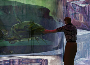 A glass catfish fits in a glass. A 1 inch high man is in front of the glass. He is facing the catfish. He is 0.2 inch above the ground. The ground is shiny. Camera light is black. The shirt of the man is [black]. The azimuth of the sun is 80 degrees. A purple light is above the man. A dim red light is left of the man. The ground is 250 feet high. A small silver pyramid is left of the glass.