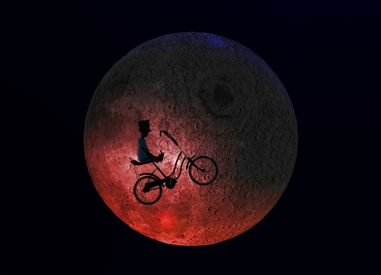 Input text: The sky is black. A tiny black bicycle is in front of and -3 feet above a huge moon. It is facing east. It is leaning back. The ground is invisible. Camera light is black. A huge red light is below the bicycle. A scarlet light is -10 inch in front of the bicycle. A scarlet light is left of and below the light. The handlebar of the bicycle is black. A very tiny dark boy is -8 inch above and -8 inch left of the bicycle. He is facing east. The azimuth of the sun is 10 degrees. The altitude of the sun is 50 degrees. The sun is navy. A dim orange light is left of and -20 feet above the moon.