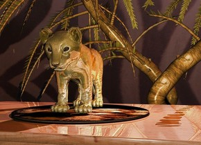 A [life] circle is on a shiny table. A gold lion is on the circle. The ground is clear. The azimuth of the sun is 20 degrees. Camera light is cream. Ambient light is black. An orange light is right of the lion. A plant is 12 feet behind and -6 feet right of the table. It is -1 foot above the ground. A plant is -11 feet left of the plant. It is facing north. The sky is 2000 feet wide [africa]. The sky is 30% dark. The sun is pink. A dim red light is above and behind the tree.