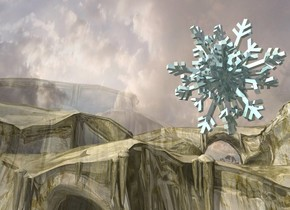 A shiny pale cyan snowflake is 4 feet above the ground. The ground is gold. Camera light is black. A clear wall is right of the snowflake. It is on the ground. It is facing east.