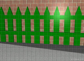 The green fence is in front of a big brick wall. A light is above the brick wall. The dirty ground is grey asphalt.