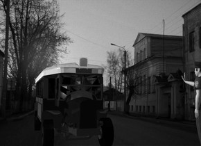 A dark bus. A [town] backdrop. It is dusk. A red light is in front of and above the bus. A navy light is left of and above and in front of the bus. Ambient light is mauve. A policeman is 1.5 feet right of and 2 feet in front of the bus. He is facing the bus. Camera light is black. A lemon light is 3 feet left of the bus.