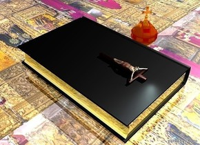 a 12 feet tall book.it is face up.a small cross is above the book.it is face up.the book's book cover is black.the book's page is gold.the cross is -6 feet behind the book.the ground is [religion].the ground is 50 feet wide.the [religion] is 20 feet tall.the ground is shiny.a sea mist blue light is behind the cross.a 4 feet tall shiny orb is 5 inches left of the book.it is facing southwest.