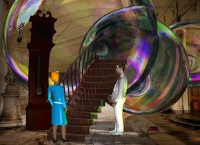 a clear cloud.the cloud is 100 feet deep.the cloud is 40 feet wide.the cloud is 30 feet tall.a shiny stairway is in front of the cloud.a woman is 1 inches in front of the stairway.she is facing the stairway.a white man is right of the stairway.he is facing the stairway.a rust light is 1 feet right of the man.fantasy sky.a large clock is 30 inches left of the stairway.a giant beetle is 1.5 feet right of the man.it is behind the man.the clock is facing southeast.a lime light is 2 inches above the beetle.the woman's hair is orange.