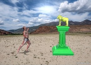 A desert backdrop. A small yellow shiny gorilla is on a shiny green pedestal facing the man, the man is facing the gorilla, the man is 5 feet away from the pedestal, the red light is 5 feet from the man. the light is 20 feet south from the man. it is noon.
