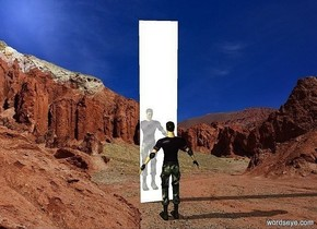 a cube.the cube is 2 inches deep.the cube is 2.5 feet wide.the cube is 12 feet tall.the cube is shiny metal.the sky is white.desert backdrop.a man is 2 feet in front of the cube.he is facing the cube.