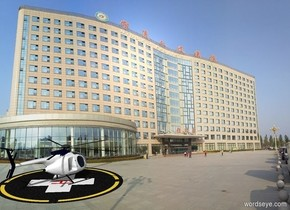 A helipad. A 64 feet deep helicopter is on the helipad. The helicopter is facing southeast. Its rotor is black. Backdrop is [hospital]. It is afternoon.
