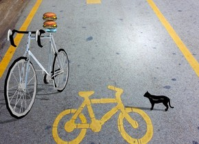The bike is silver. The bike is big. The bike is on a street. The bike is facing north. There is a first big burger above the bike's seat. There is a second big burger above the first burger. The bike's seat is sky blue. There is a little cat. The cat is black. The cat faces east. The cat is 6 feet to the left of the bike.