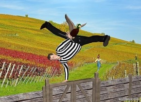 It is noon. The man is .9 feet inside of the fence. The gate of the fence is wood. The post of the fence is wood. The fence is wood. The 2 foot tall farmer is behind the man.The farmer is 1 foot to the right of the man. The farmer is facing the man. The shirt of the man is dull [stripes]. The duck is -1.7 feet above the man. The duck is -2.2 foot in front of the man.The duck is leaning 20 degrees to the left.