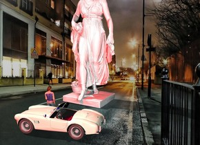 The large white statue is in the street. The small car is 4 feet in front of the statue. It is facing left. The small woman is behind and -2 feet to the left of the car. SHe is facing back. The red light is 1 foot above and behind the woman. A 2nd red light is 23 feet in front and above the car.